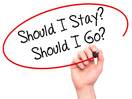 indecisiveness: Man Hand writing Should I Stay? Should I Go? with black marker on visual screen. Isolated on white. Business, technology, internet concept. Stock Photo