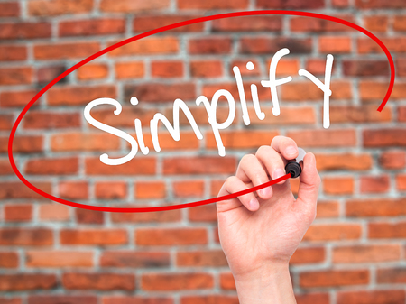 simplify: Man Hand writing Simplify with black marker on visual screen. Isolated on bricks. Business, technology, internet concept. Stock Photo Stock Photo