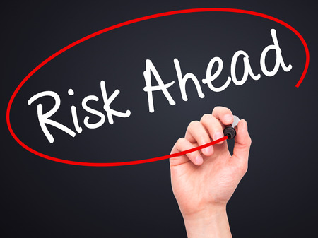 risk ahead: Man Hand writing Risk Ahead with black marker on visual screen. Isolated on black. Business, technology, internet concept. Stock Image Stock Photo