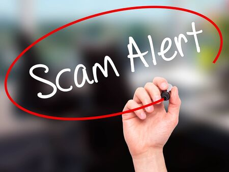 Man Hand writing Scam Alert  with black marker on visual screen. Isolated on office. Business, technology, internet concept. Stock Photo 写真素材