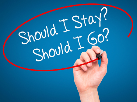 indecisiveness: Man Hand writing Should I Stay? Should I Go? with black marker on visual screen. Isolated on blue. Business, technology, internet concept. Stock Photo