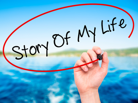 photo story: Man Hand writing Story Of My Life with black marker on visual screen. Isolated on nature. Business, technology, internet concept. Stock Photo Stock Photo