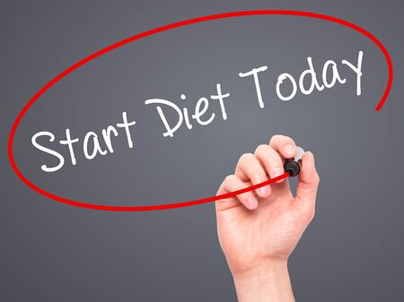 overeat: Man Hand writing Start Diet Today  with black marker on visual screen. Isolated on grey. Business, technology, internet concept. Stock Photo