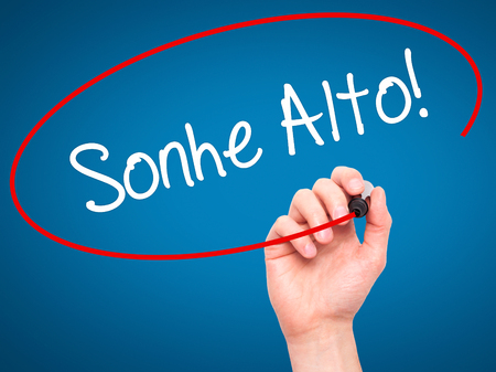 Man Hand writing Sonhe Alto! (Dream Big in Portuguese) with black marker on visual screen. Isolated on blue. Business, technology, internet concept. Stock Photo