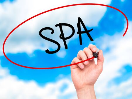 revitalize: Man Hand writing SPA with black marker on visual screen. Isolated on sky. Business, technology, internet concept. Stock Photo Stock Photo