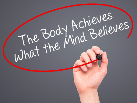 believes: Man Hand writing The Body Achieves What the Mind Believes with black marker on visual screen. Isolated on grey.