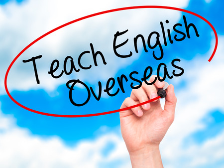 Man Hand writing Teach English Overseas with black marker on visual screen. Isolated on sky.