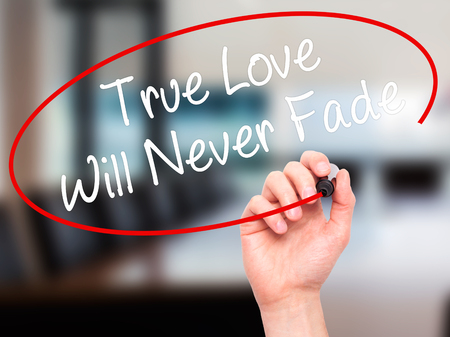 with true love: Man Hand writing True Love Will Never Fade with black marker on visual screen. Isolated on background.