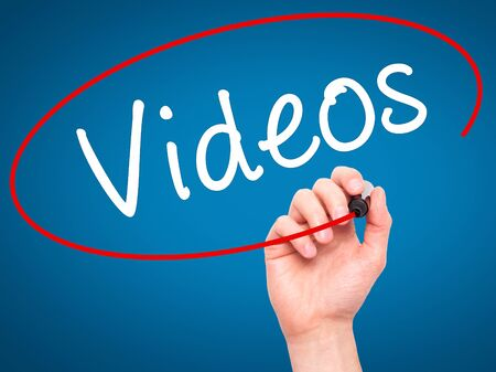 infomercial: Man Hand writing Videos with black marker on visual screen. Isolated on blue. Stock Photo