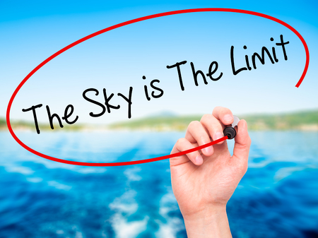 sky is the limit: Man Hand writing The Sky is The Limit  with black marker on visual screen. Isolated on nature.