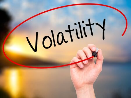 volatility: Man Hand writing Volatility with black marker on visual screen. Isolated on nature. Stock Photo