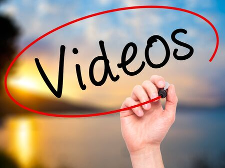 infomercial: Man Hand writing Videos with black marker on visual screen. Isolated on nature. Stock Photo