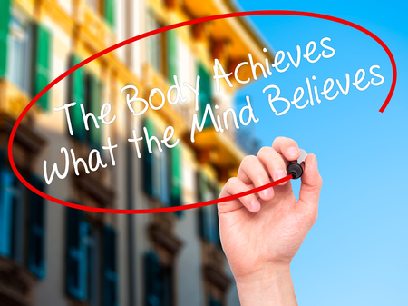 believes: Man Hand writing The Body Achieves What the Mind Believes with black marker on visual screen. Isolated on city. Stock Photo