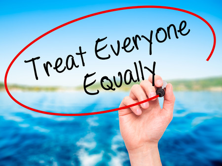everyone: Man Hand writing Treat Everyone Equally with black marker on visual screen. Isolated on background. Stock Photo