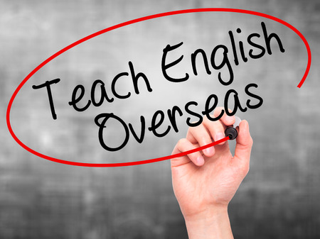 Man Hand writing Teach English Overseas with black marker on visual screen. Isolated on grey. Stock Photo