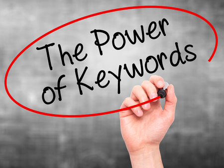 Man Hand writing The Power of Keywords with black marker on visual screen. Isolated on grey. Stock Photo