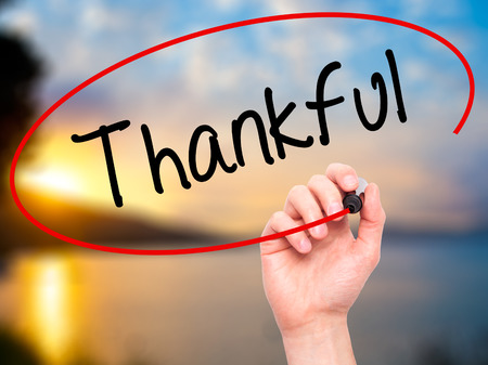 obliged: Man Hand writing Thankful with black marker on visual screen. Isolated on background.