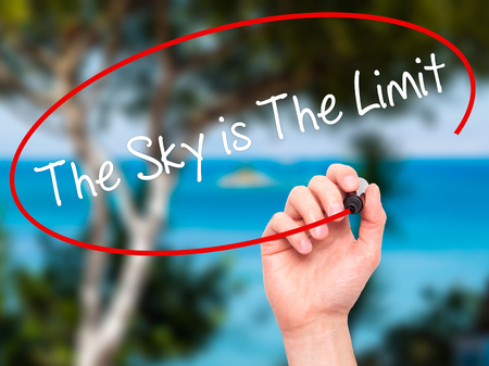 sky is the limit: Man Hand writing The Sky is The Limit with black marker on visual screen. Isolated on nature. Stock Photo