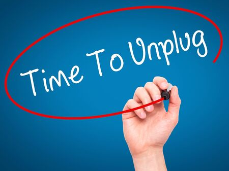 unplug: Man Hand writing Time To Unplug with black marker on visual screen. Isolated on blue Stock Photo