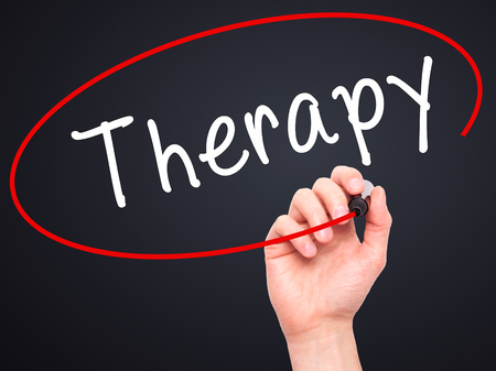 visual therapy: Man Hand writing Therapy with black marker on visual screen. Isolated on black. Stock Photo