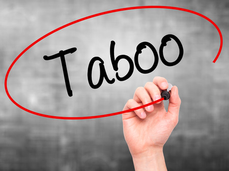 Man Hand writing Taboo with black marker on visual screen. Isolated on background. Business, technology, internet concept. Stock Photo