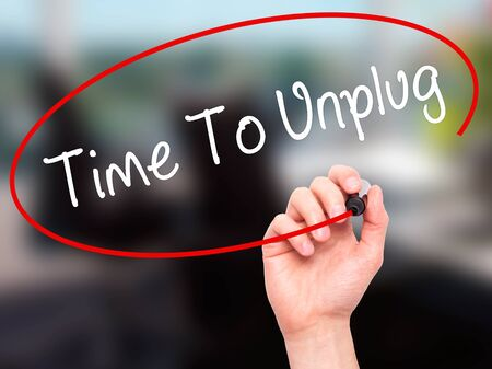 unplugging: Man Hand writing Time To Unplug with black marker on visual screen. Isolated on office. Business, technology, internet concept. Stock Photo