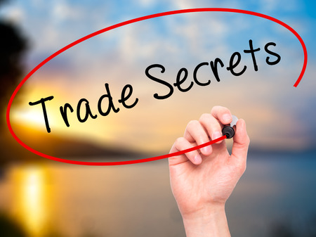 privileged: Man Hand writing Trade Secrets with black marker on visual screen. Isolated on nature. Business, technology, internet concept. Stock Photo