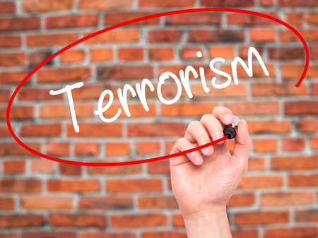 cyber terrorism: Man Hand writing Terrorism with black marker on visual screen. Isolated on bricks. Business, technology, internet concept.