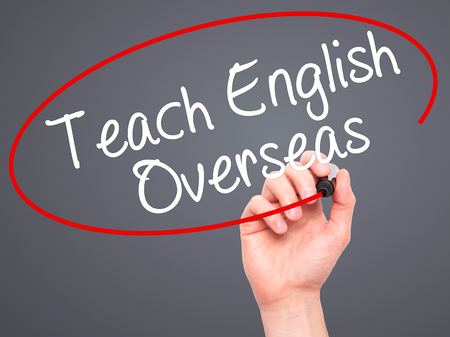Man Hand writing Teach English Overseas with black marker on visual screen. Isolated on grey. Business, technology, internet concept. Stock Photo