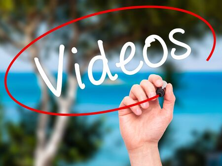 televisor: Man Hand writing Videos with black marker on visual screen. Isolated on nature. Business, technology, internet concept. Stock Image