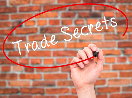 secret code: Man Hand writing Trade Secrets with black marker on visual screen. Isolated on bricks. Business, technology, internet concept. Stock Photo