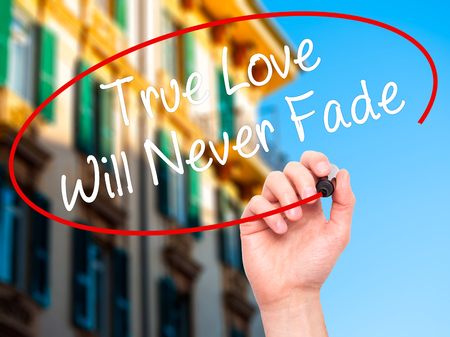 in loving memory: Man Hand writing True Love Will Never Fade with black marker on visual screen. Isolated on background. Business, technology, internet concept. Stock Photo Stock Photo