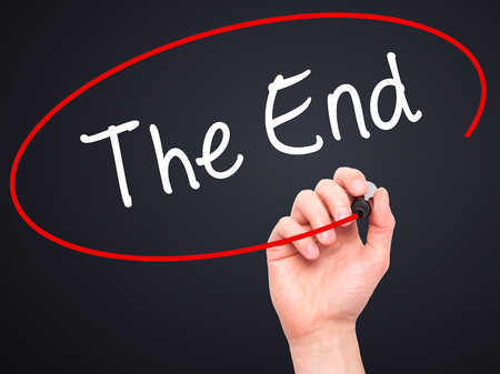 conclusive: Man Hand writing The End with black marker on visual screen. Isolated on black. Business, technology, internet concept. Stock Photo