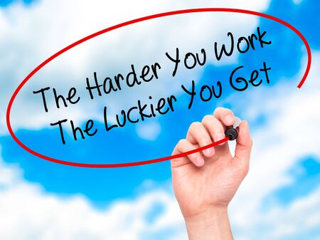 harder: Man Hand writing The Harder You Work The Luckier You Get  with black marker on visual screen. Isolated on sky. Business, technology, internet concept. Stock Photo