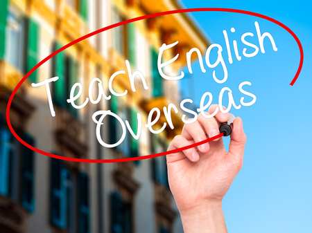 oportunity: Man Hand writing Teach English Overseas with black marker on visual screen. Isolated on city. Business, technology, internet concept. Stock Photo