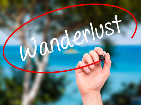 wanderlust: Man Hand writing Wanderlust with black marker on visual screen. Isolated on nature. Business, technology, internet concept. Stock Photo