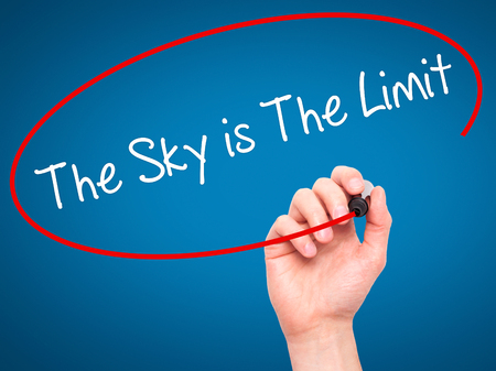 sky is the limit: Man Hand writing The Sky is The Limit  with black marker on visual screen. Isolated on blue. Business, technology, internet concept. Stock Photo Stock Photo