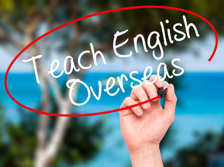 recruiters: Man Hand writing Teach English Overseas with black marker on visual screen. Isolated on nature. Business, technology, internet concept. Stock Photo