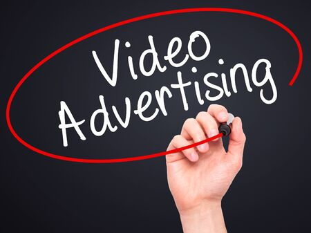 infomercial: Man Hand writing Video Advertising with black marker on visual screen. Isolated on black. Business, technology, internet concept. Stock Photo