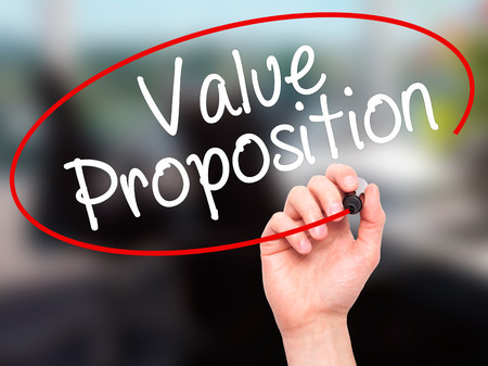 resonating: Man Hand writing Value Proposition with black marker on visual screen. Isolated on office. Business, technology, internet concept. Stock Photo