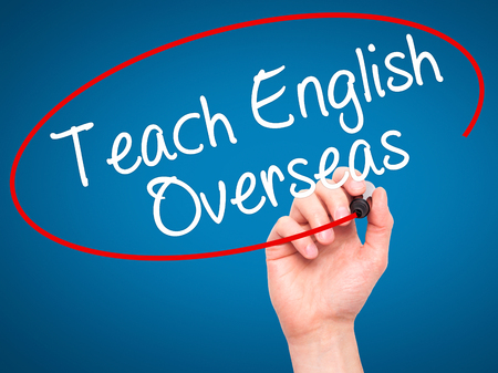 Man Hand writing Teach English Overseas with black marker on visual screen. Isolated on blue. Business, technology, internet concept. Stock Photo