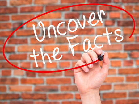 uncover: Man Hand writing Uncover the Facts with black marker on visual screen. Isolated on bricks. Business, technology, internet concept. Stock Image