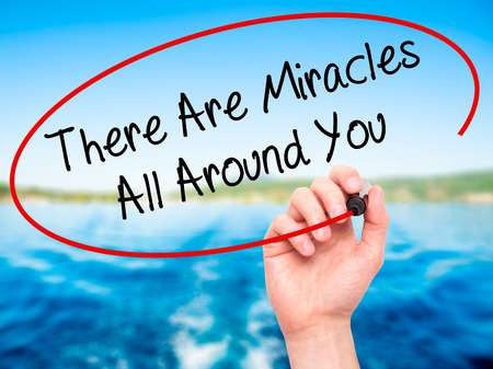 Man Hand writing There Are Miracles All Around You with black marker on visual screen. Isolated on nature. Business, technology, internet concept. Stock Photo