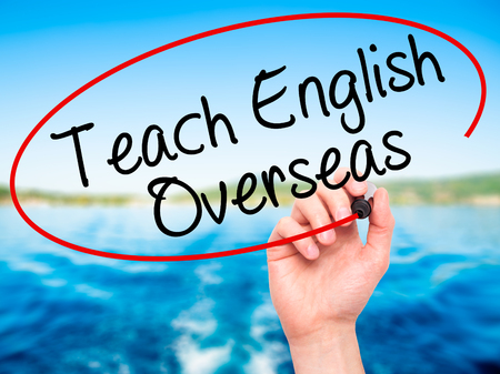oportunity: Man Hand writing Teach English Overseas with black marker on visual screen. Isolated on nature. Business, technology, internet concept. Stock Photo