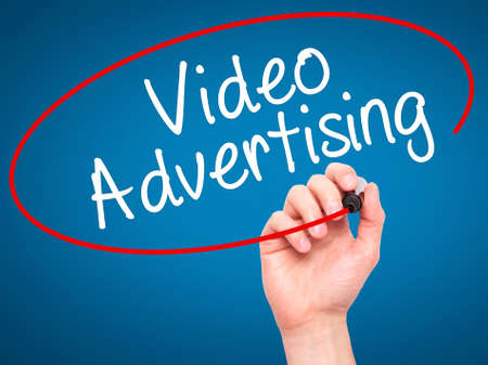 infomercial: Man Hand writing Video Advertising with black marker on visual screen. Isolated on blue. Business, technology, internet concept. Stock Photo