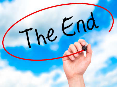 conclusive: Man Hand writing The End with black marker on visual screen. Isolated on sky. Business, technology, internet concept. Stock Photo