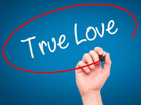 with true love: Man Hand writing True Love with black marker on visual screen. Isolated on blue. Business, technology, internet concept. Stock Photo Stock Photo