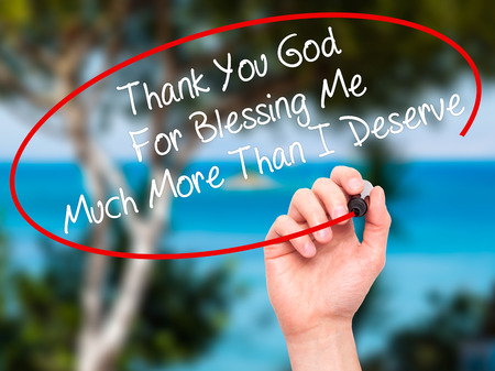 deserve: Man Hand writing Thank You God For Blessing Me Much More Than I Deserve with black marker on visual screen. Isolated on nature. Business, technology, internet concept. Stock Photo