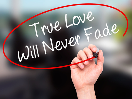 need direction: Man Hand writing True Love Will Never Fade with black marker on visual screen. Isolated on background. Business, technology, internet concept. Stock Photo Stock Photo