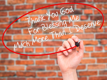 deserve: Man Hand writing Thank You God For Blessing Me Much More Than I Deserve with black marker on visual screen. Isolated on bricks. Business, technology, internet concept. Stock Photo Stock Photo